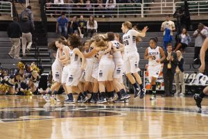 The Lady Blue Devils celebrate after beating Dexter in the state semi-finals. They will play Grand Haven in the state finals.